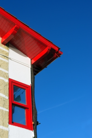 House facade with red roof and window against blue sky in Puerto Viejo, Getxo.
