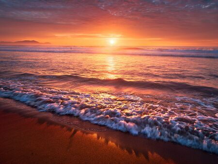 beautiful red sunset on beach with a wave on the shore