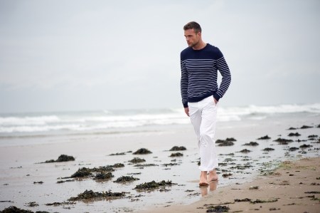 A young man walking on the beach in Western Europe