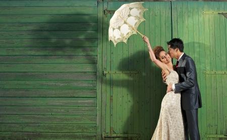 Foto de Fun image of a beautiful bride in vintage wedding dress being kissed by a handsome man on a farm - Imagen libre de derechos