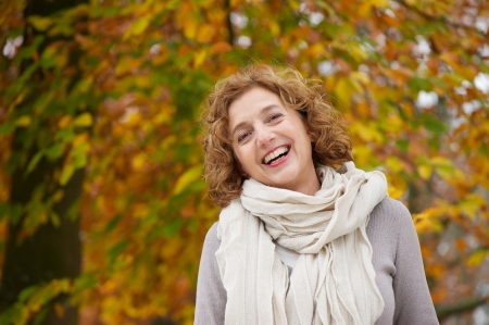 Mature woman smiling in autumn. A beautiful yellow leaves background