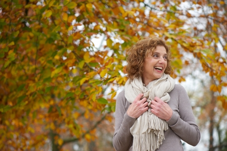 Middle age woman smile in autumn.Beautiful  Yellow leaves background