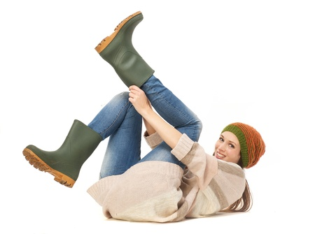 Photo pour Young woman smiling and putting on gardening boots  Isolated on white background - image libre de droit