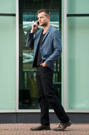 Handsome young man walking and talking on mobile phone in the city