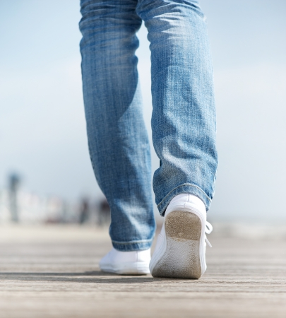 Close up of a woman walking outdoors in comfortable white shoes