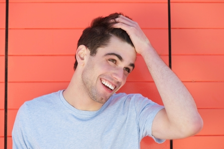 Photo pour Portrait of an attractive young man smiling with hand in hair - image libre de droit