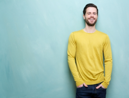 Portrait of a handsome young man smiling against blue background