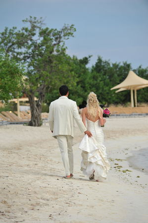 Rear view portrait of a bride and groom walking on beachの写真素材
