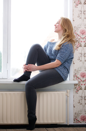 Portrait of a young woman sitting on windowsill and looking out window