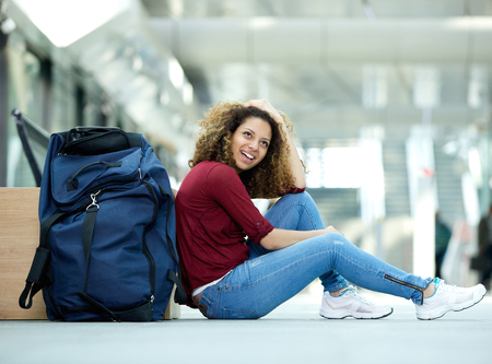 Portrait of a young woman smiling with bag at station