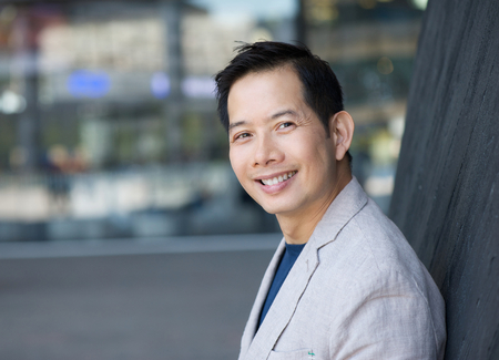 Close up portrait of a trendy asian man smiling outdoorsの写真素材