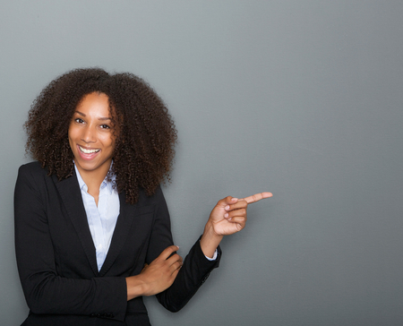 Close up portrait of a smiling business woman pointing finger showing copy space