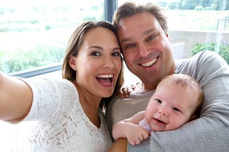 Close up portrait of a happy couple taking a selfie with baby