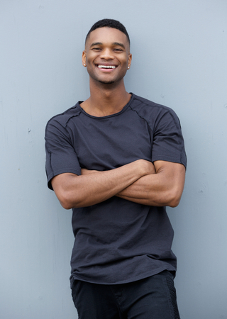 Portrait of a friendly black man smiling with arms crossed against gray background