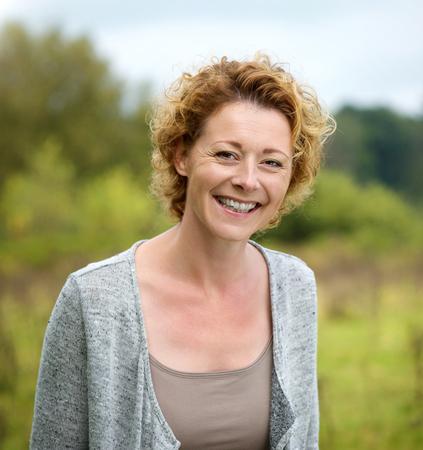 Foto für Close up portrait of a beautiful mature woman smiling in the park - Lizenzfreies Bild