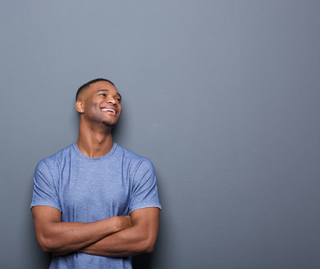 Portrait of a happy african man laughing with arms crossed on gray background