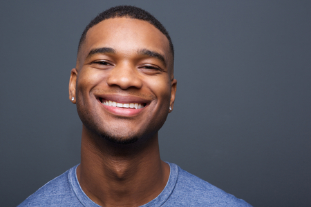 Close up portrait of a happy black man smiling on gray background