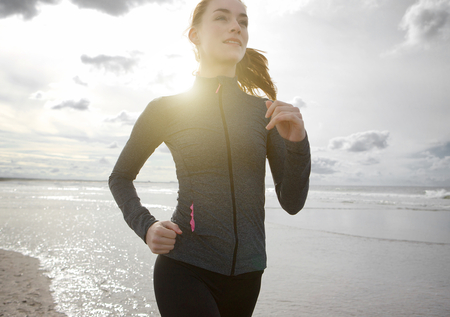 Close up portrait of a woman jogging outdoors by the beach
