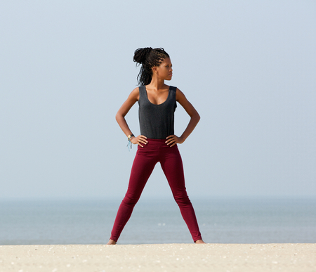 Portrait of a young black woman standing at beach with hand on hips