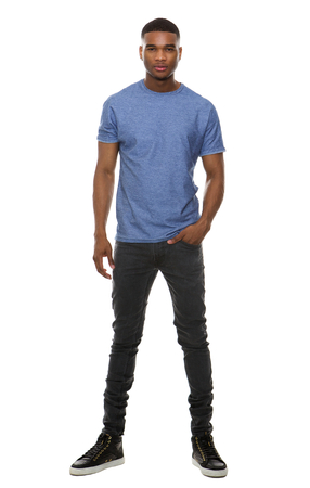 Full length portrait of a fashionable young man standing on isolated white background