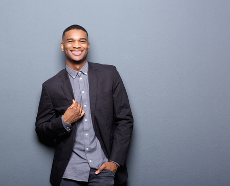 Photo for Portrait of a fashionable african american man smiling on gray background - Royalty Free Image