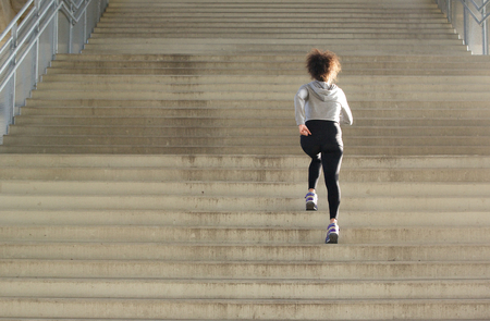Rear view young female athlete running up stairs