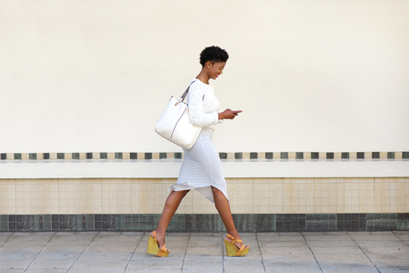 Full length side portrait of a young woman walking and sending text message on cell phoneの写真素材