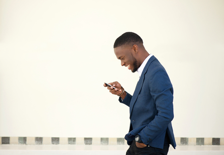 Foto de Side portrait of a smiling businessman walking and sending text message on mobile phone - Imagen libre de derechos