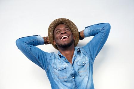Foto de Close up portrait of a young man laughing with hands behind head on white background - Imagen libre de derechos