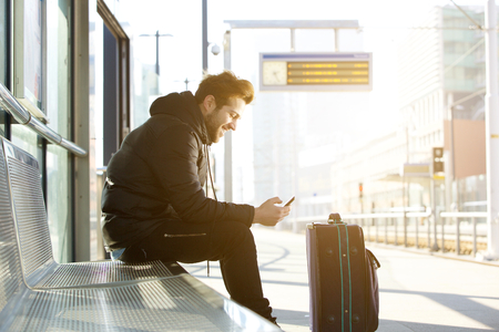 Photo pour Side portrait of a smiling young man sitting with mobile phone and bag waiting for train - image libre de droit