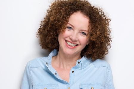 Foto für Close up portrait of a cheerful middle aged woman smiling against white background - Lizenzfreies Bild