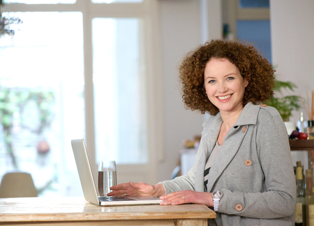 Photo for Portrait of a happy middle aged woman using laptop at home - Royalty Free Image
