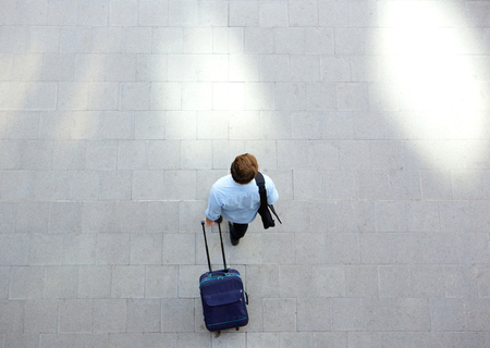 Photo pour Portrait from above of a young man walking with luggage at station - image libre de droit