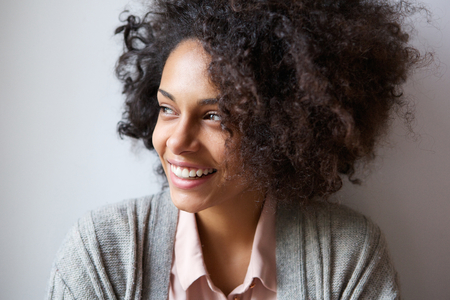 Close up portrait of a beautiful black woman smiling and looking away