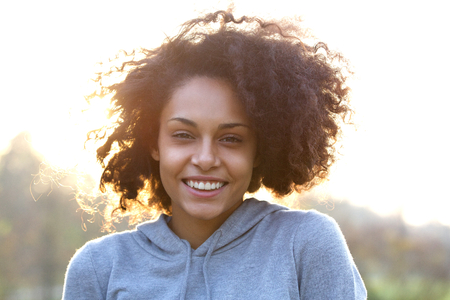 Close up portrait of a happy smiling young woman with curly hairの写真素材