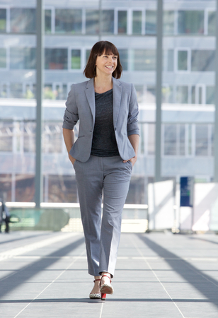 Full length portrait of a relaxed business woman smiling and walking