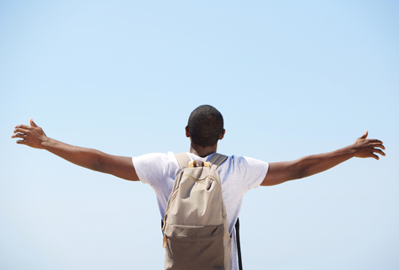 Young black man standing with arms outstretched from behind