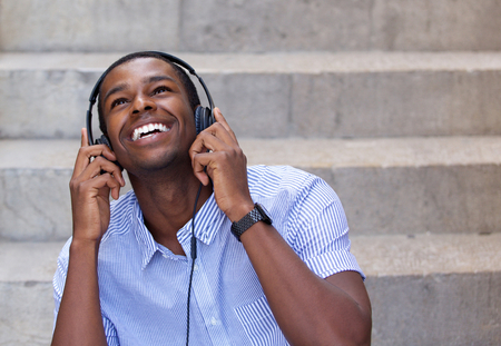 Close up portrait of a smiling young man listening to music on headphones and looking up
