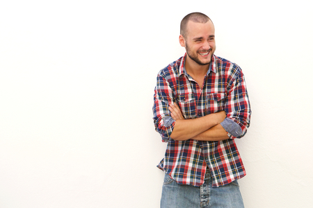 Young man laughing and looking away standing against white background with arms crossed