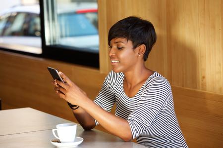 Foto de Portrait of a beautiful young african american woman reading text message on mobile phone - Imagen libre de derechos