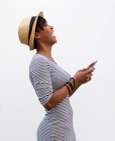 Photo for Side portrait of a young woman laughing and holding mobile phone - Royalty Free Image