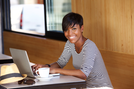 Portrait of a smiling young black woman using laptopの写真素材