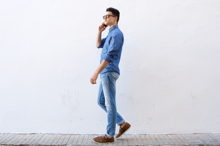 Photo pour Full body side portrait of a handsome young man walking and talking on cell phone - image libre de droit