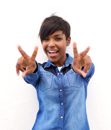 Portrait of a cheerful african american woman with peace hand sign