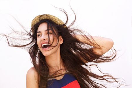 Portrait of a smiling young woman with long hair blowing in the windの写真素材