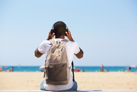 Young man sitting by beach with bag listening to music on headphones