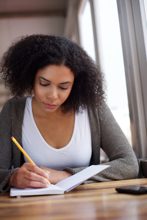 Close up portrait of a young african american female student writing in book