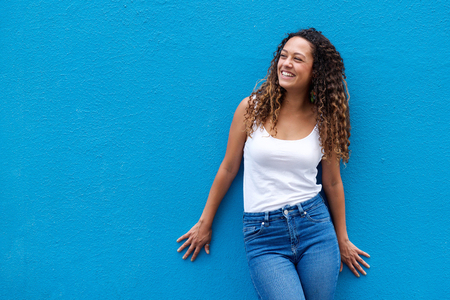 Photo for Portrait of young woman smiling looking away against blue background - Royalty Free Image
