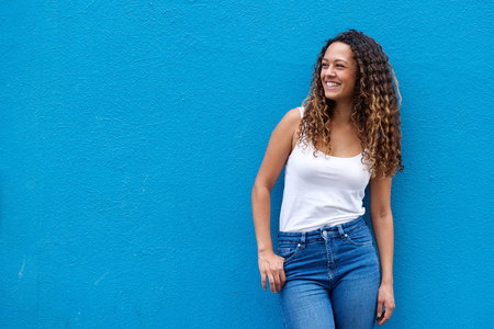Photo pour Portrait of young woman with curly hair smiling against a blue wall looking away - image libre de droit