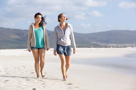 Foto de Portrait of two smiling women friends walking on beach together - Imagen libre de derechos